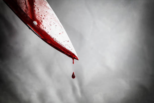 close-up of man holding knife smeared with blood and still dripping. - foto stock
