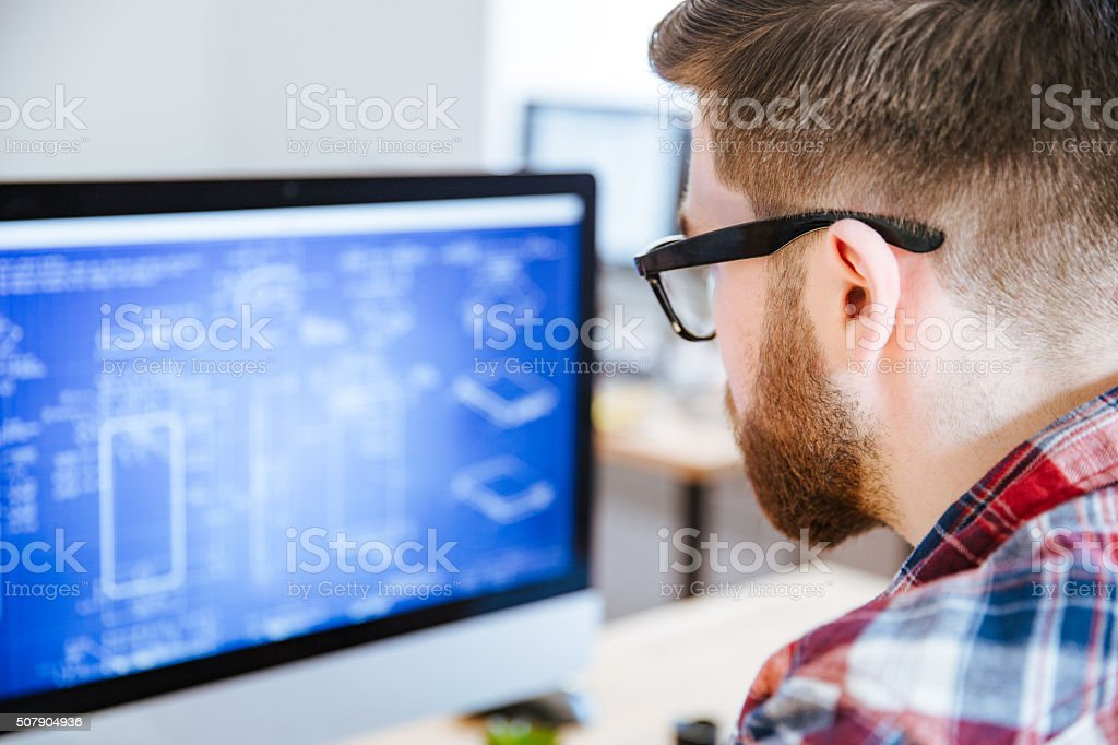 Closeup of man in glasses making blueprints on computer stock photo