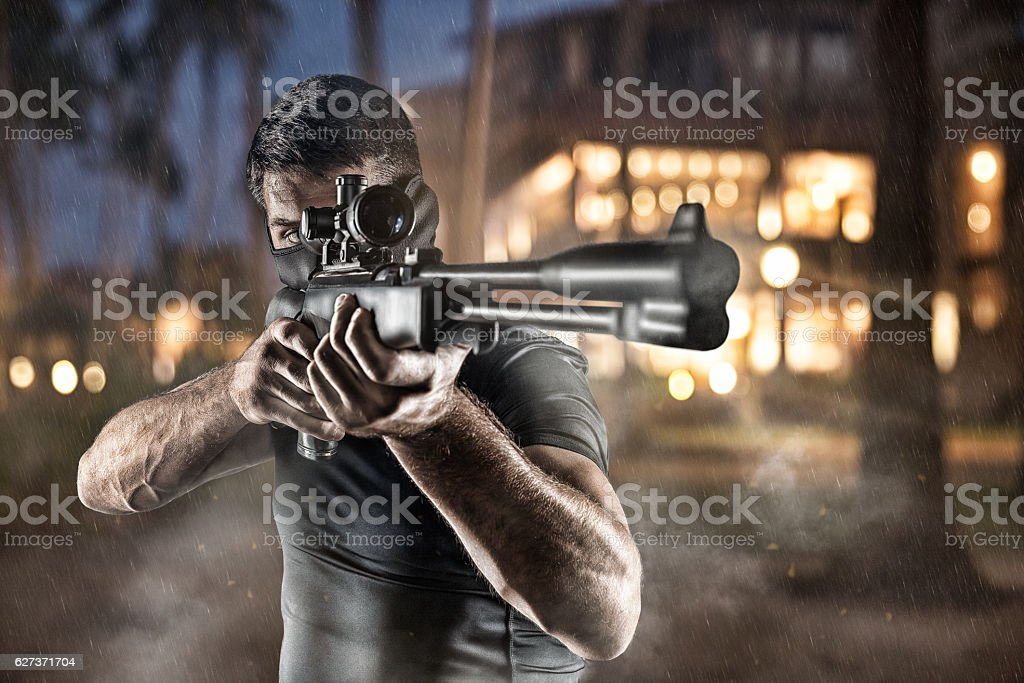 Close-up of man in headgear aiming with sniper rifle stock photo