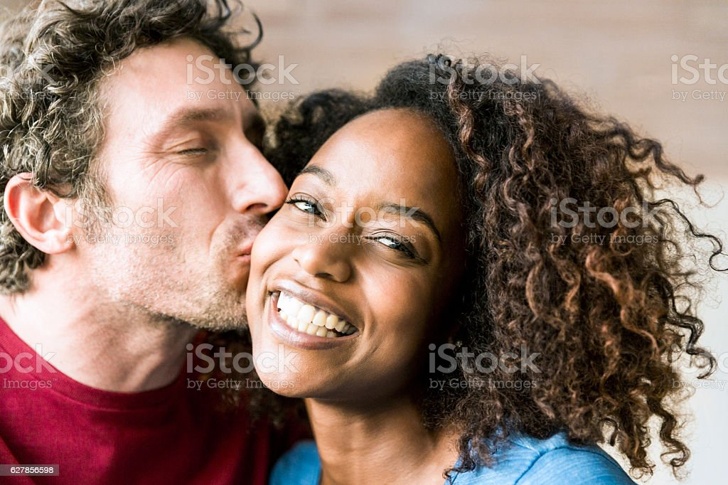Close-up of man kissing cheerful woman on cheek stock photo