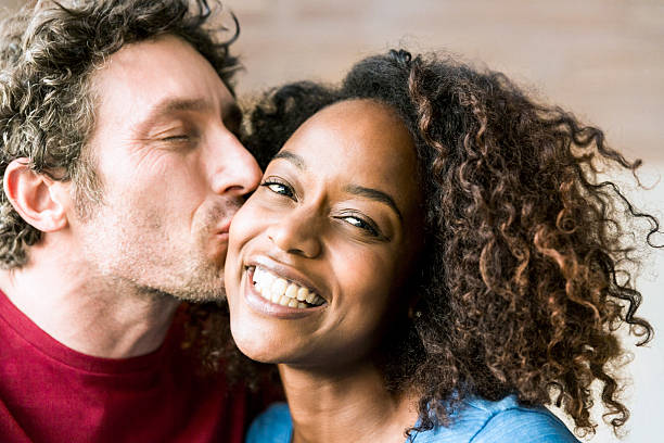 Close-up of man kissing cheerful woman on cheek stock photo