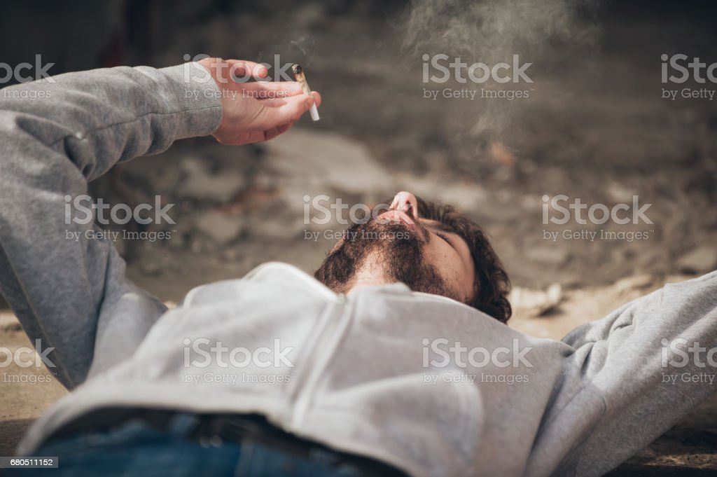 Closeup of man lying on the ground and smoke joint royalty-free stock photo