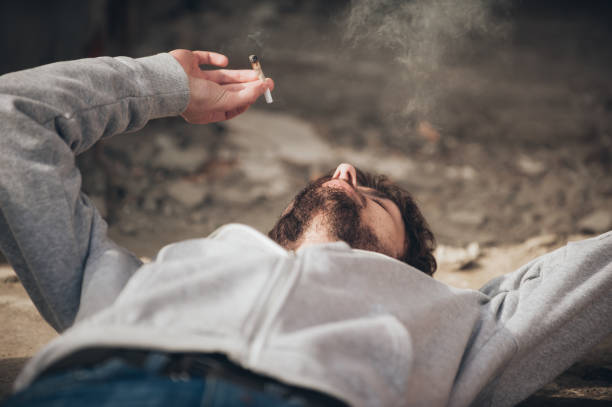 Closeup of man lying on the ground and smoke joint stock photo