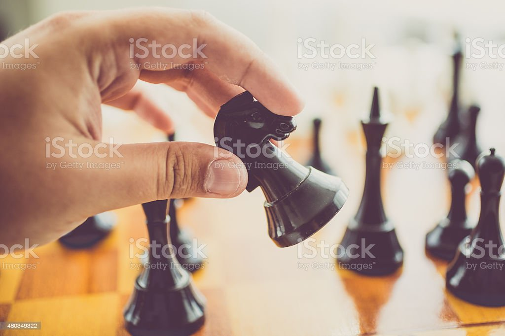 closeup of man making move with black piece at chess stock photo