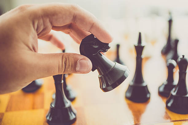 closeup of man making move with black piece at chess - position stock pictures, royalty-free photos & images