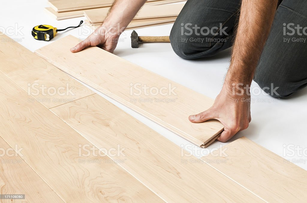 Close-up of man putting hardwood floor panels, floorboards stock photo