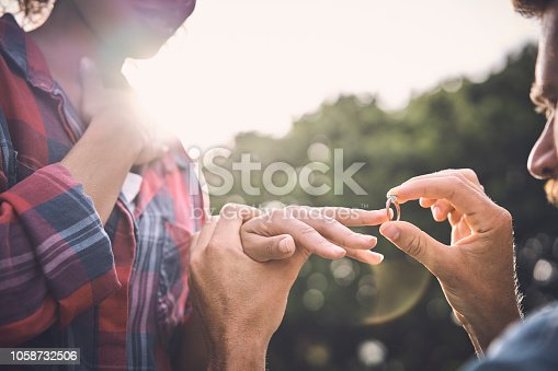 Back lit of man putting engagement ring on girlfriend's finger at back yard. Close-up of woman standing while boyfriend proposing outdoors. They are spending leisure time.