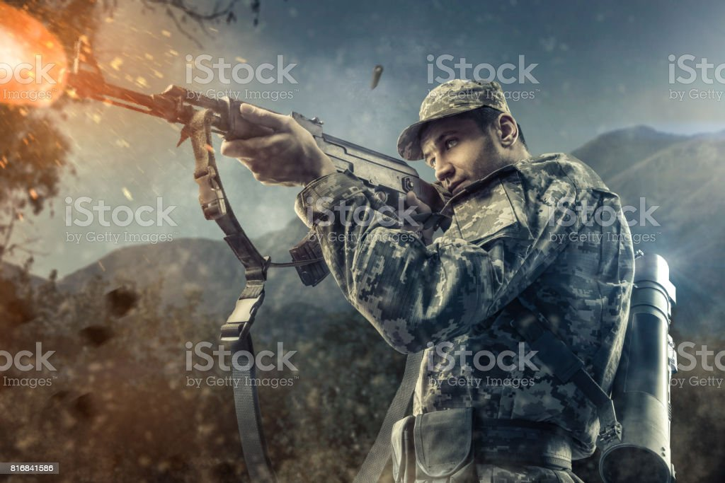 Close-up of man shooting with machine gun stock photo