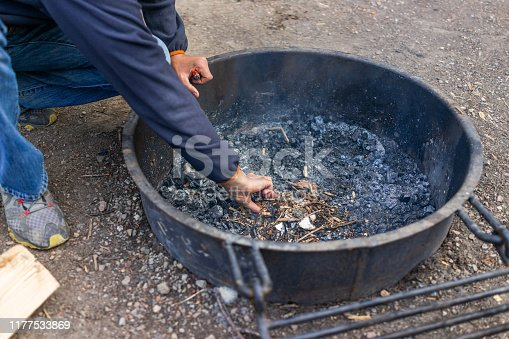 Closeup of man starting fire at campground campfire grill in outdoor park with leaves and twigs on cold evening