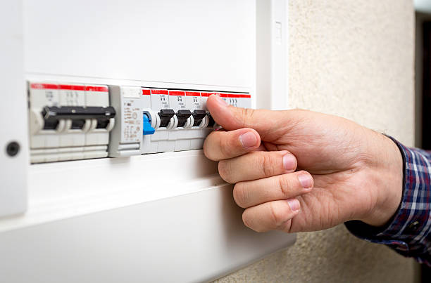 closeup of man switching on fuseboard - fuse box stock photos and pictures