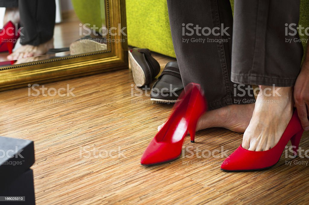 Close-up of man trying on red woman's high-heels, wardrobe interior stock photo
