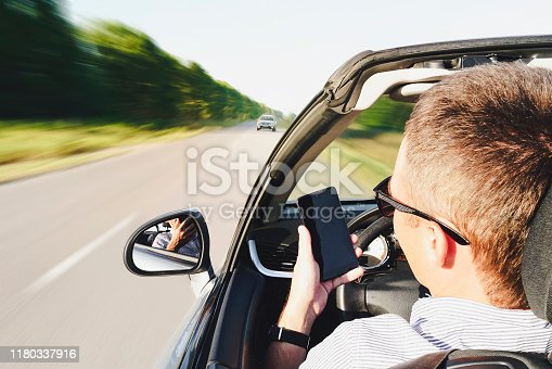 closeup of a man using a smartphone while driving a car. driving into oncoming traffic. Dangerous movement. Distracted by phone. The guy writes a message in phone while driving. effect blurred motion