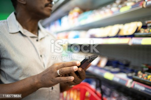 1184048369 istock photo Close-up of man using mobile phone in supermarket 1183778834