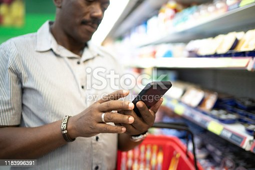 1184048369 istock photo Close-up of man using mobile phone in supermarket 1183996391
