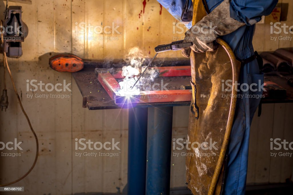 Closeup of man wearing mask welding in a workshop royalty-free stock photo