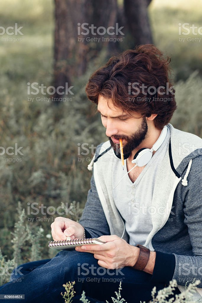 Close-up of man with notebook biting pencil stock photo