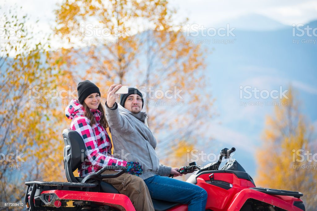 Close-up of man with woman in winter clothing on red quad bike makes selfie on the phone against blurred background of autumn landscape with mountains and yellow trees stock photo