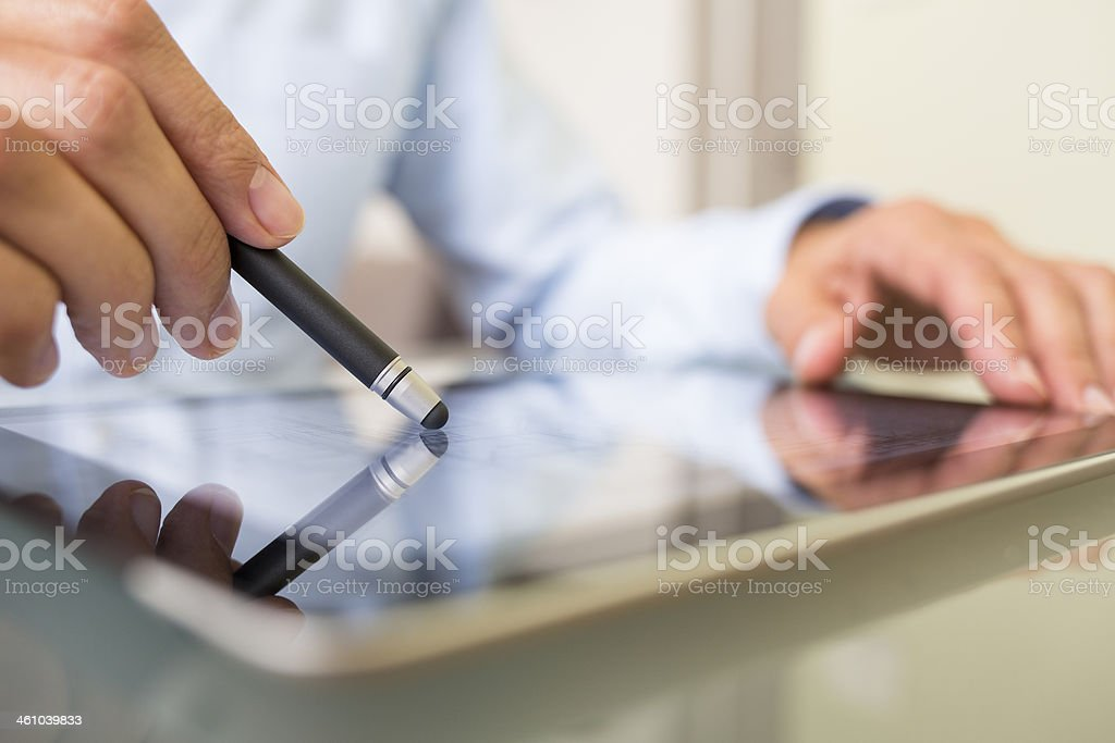 Close-up of man working with stylus and digital tablet pc stock photo