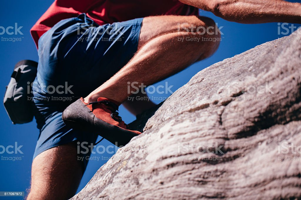 Closeup of man's climbing shoes during bouldering on rock stock photo