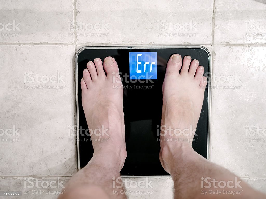Closeup of man's feet on weight scale indicating error stock photo