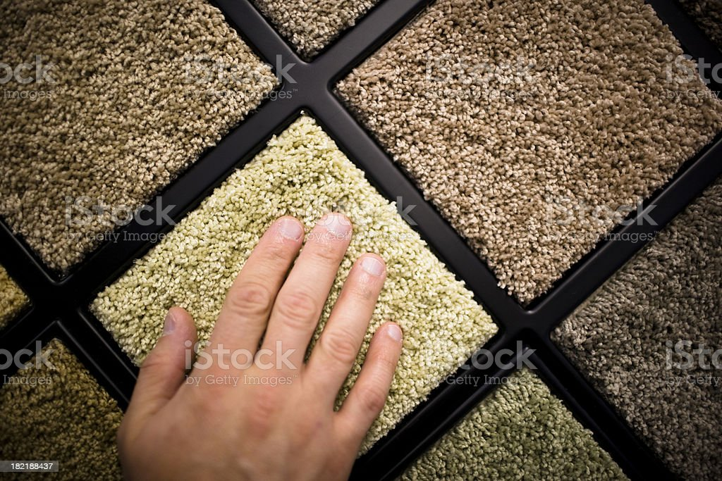 Close-up of man's hand feeling carpet samples royalty-free stock photo