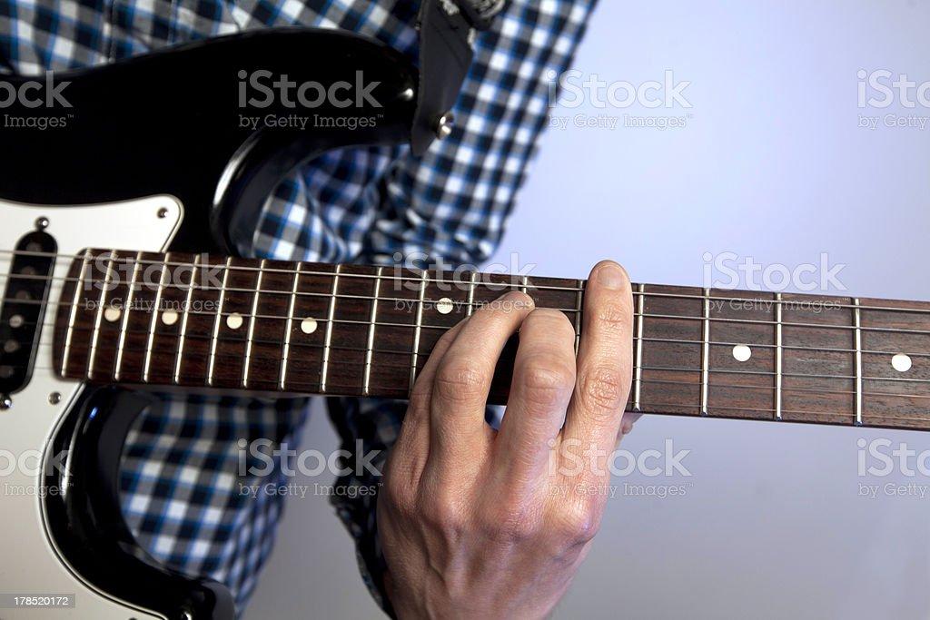 Closeup of man's hand on guitar frets stock photo