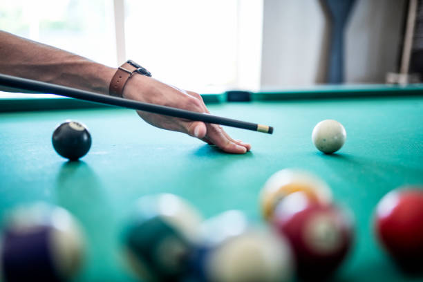 close-up of man's hand preparing to hit pool ball - pool cue stock photos and pictures