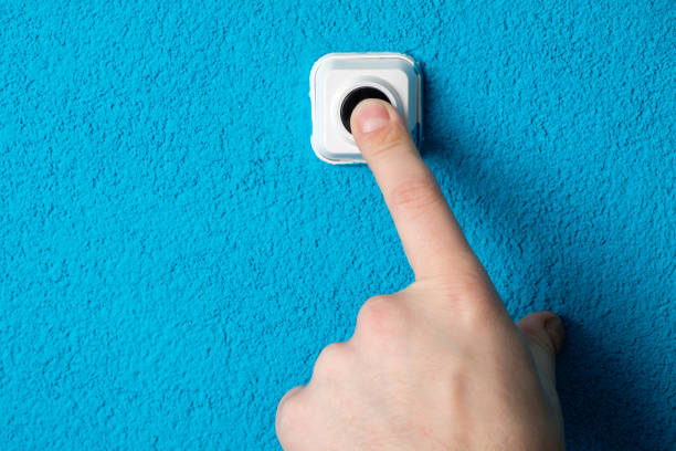 close-up of man's hand pressing the button of doorbell on blue wall - squillare foto e immagini stock