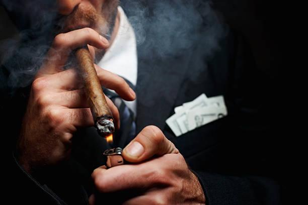 zbliżenie człowiek rękę z cygarem i lżejszy - gangster zdjęcia i obrazy z banku zdjęć