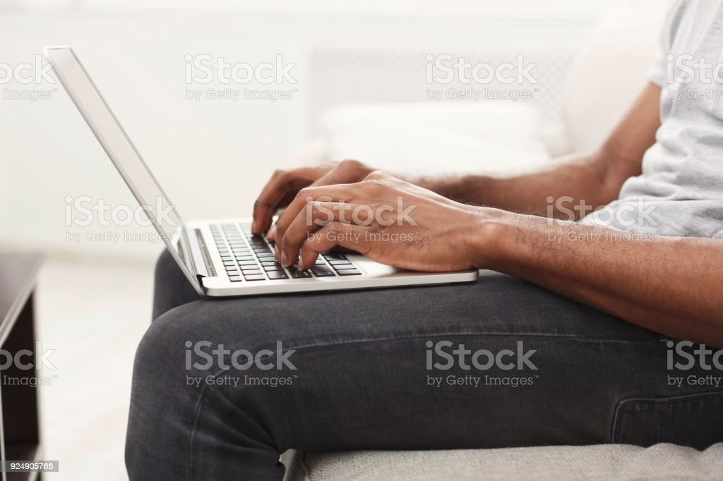 Closeup of man's hands on laptop keyboard stock photo