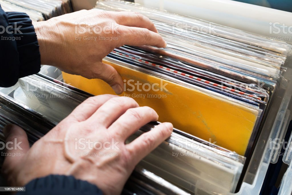 Close-up of man\'s hands, searching a second hand vinyl record in a...