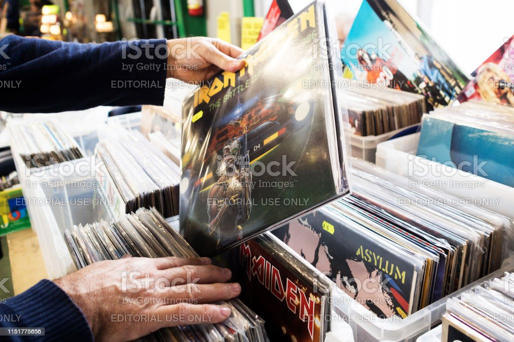 Man sift through boxes of vintage records in a flea market sale...