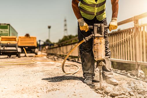 Unrecognizable manual worker using pneumatic hammer drill and repairing bridge.
