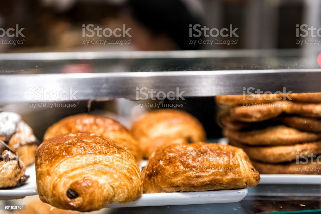 Closeup of many golden baked chocolate crisp croissants on glass shelf tray display desserts sweets in bakery shop cafe store stock photo