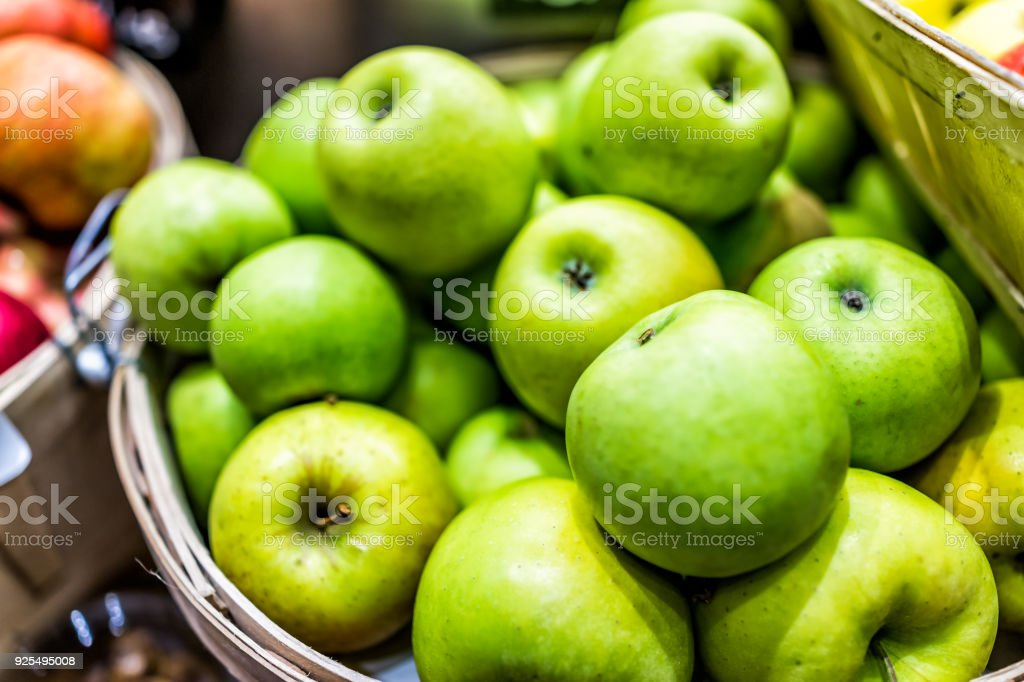 Closeup of many granny smith green yellow apples in wooden basket at farmer's market shop store showing detail and texture stock photo