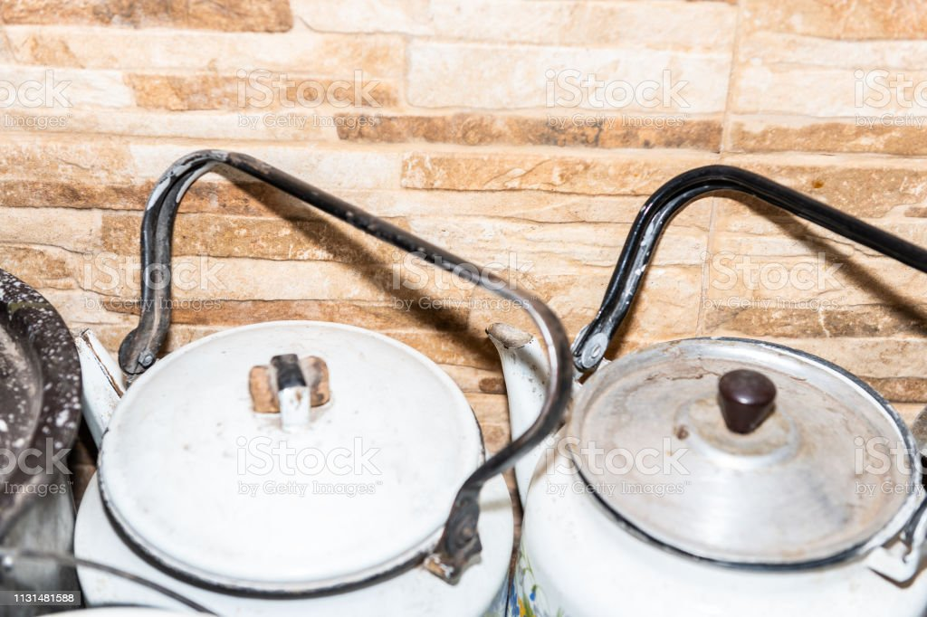 Closeup of many large pots and pans kettle teapots lids on rustic...