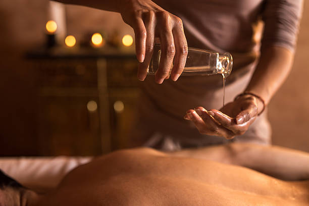 Close-up of massage therapist pouring massage oil in hand. stock photo