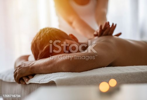 Masseur doing back massage on man body in the spa salon. Beauty treatment concept. Girl in a T-shirt doing a massage to a guy. Candles in the foreground. Man lying on the table on a white background.