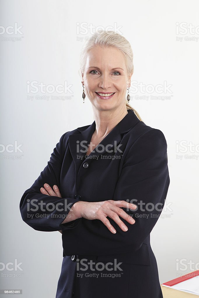 Close-up of mature businesswoman smilling with arms crossed royalty-free stock photo