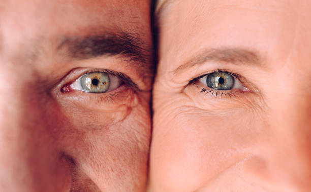Close-up of mature man and woman's faces with green eyes stock photo