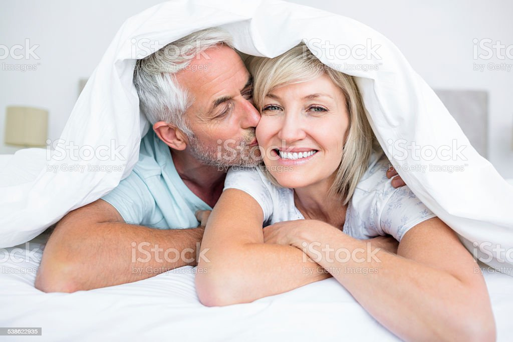 Closeup of mature man kissing womans cheek in bed stock photo