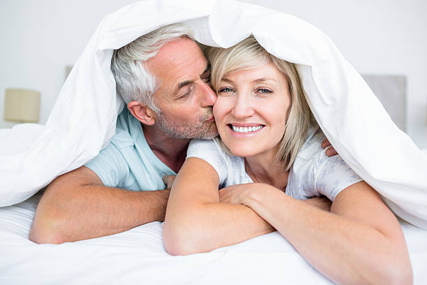 closeup of mature man kissing womans cheek in bed - ouder volwassenen koppel stockfoto's en -beelden