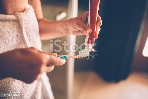 Close-up of senior woman's hands squeezing and applying toothpaste on toothbrush to brush her teeth
