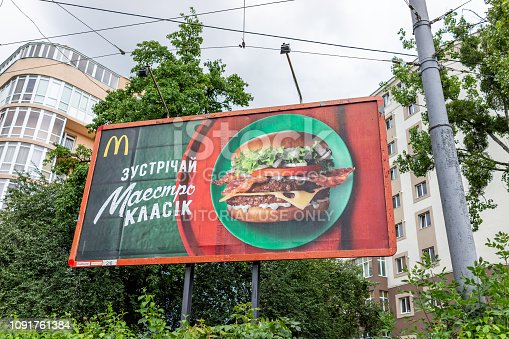 Rivne, Ukraine - July 23, 2018: Closeup of Mcdonalds advertisement ad banner sign in Ukrainian city by street buildings, cyrillic and burger picture