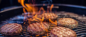Close-up of juicy burger patties on a ribbed barbecue, flames enveloping the meat.