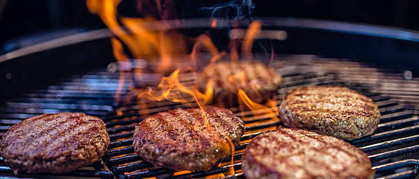 close-up of meat patties on a barbecue - barbecue grill stock photos and pictures