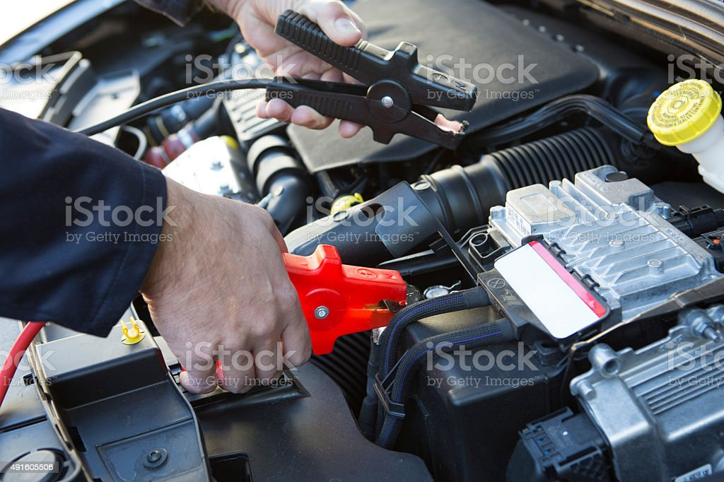 Close-Up Of Mechanic Attaching Jumper Cables To Car Battery stock photo