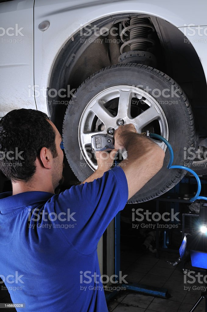 Close-up of mechanic fixing car tire royalty-free stock photo