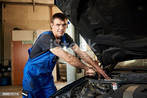 962888586 istock photo Close-up of mechanic in a dirty work uniform repairs a car in his repair shop. The bonnet is open, the guy looks at the camera 899675114