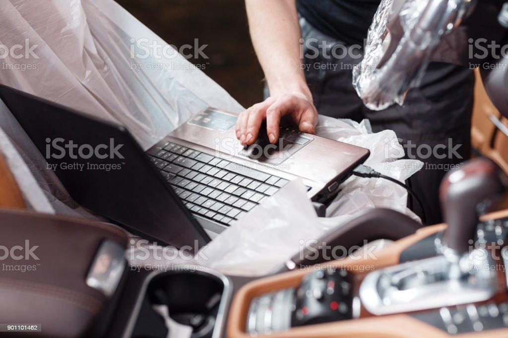 Nahaufnahme der Mechaniker mit digitalen Laptop während der Prüfung Automotor in Garage. Schließen Sie den Sensor-Stecker am Fahrzeug – Foto